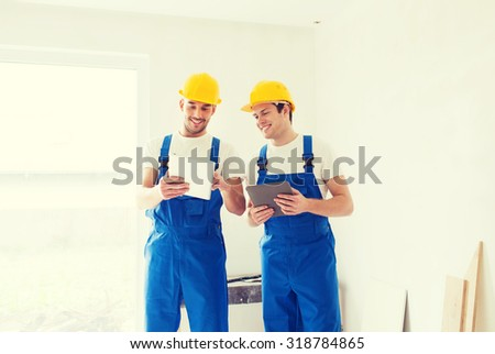 building, renovation, technology, electricity and people concept - two builders with tablet pc computers indoors - stock photo