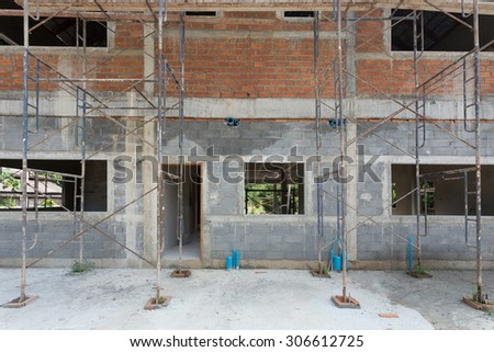 building residential construction house with scaffold steel for construction worker, wall made from brick - stock photo
