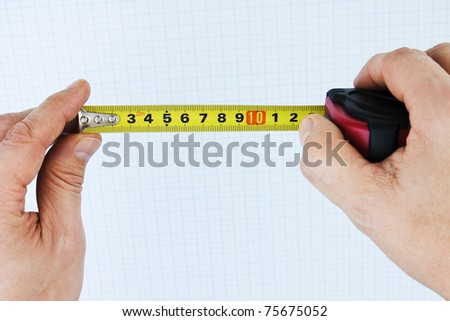 Building Roulette in the hands against the background of graph paper