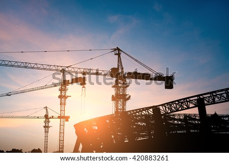 Building site with high-rise block under construction in an urban environment dominated by a large industrial crane silhouetted against a cloudy blue sky - stock photo
