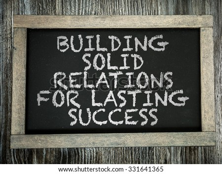 Building Solid Relations For Lasting Success written on chalkboard - stock photo
