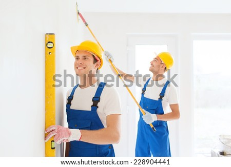 building, teamwork and people concept - group of smiling builders in hardhats with tools indoors - stock photo