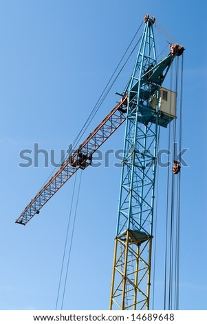 building tower crane against the blue sky