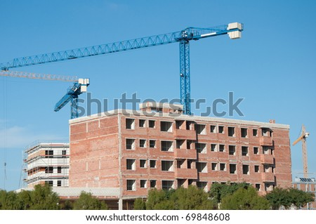 building under construction and cranes - stock photo