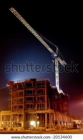 Building under construction illuminated at night - stock photo