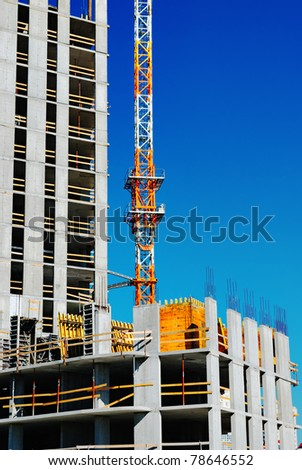 Building under construction with crane on blue sky. Industrial image - stock photo