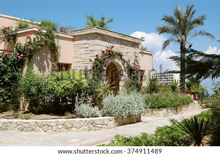 Building with arched entrance and roses in  Greek luxury hotel.
