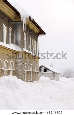 Building with the plenty of snow in front of windows and heavy icicles on the roof