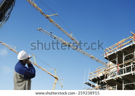 building worker directing large construction cranes - stock photo