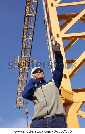 building worker, engineer, with large construction crane in background - stock photo