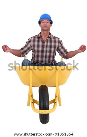 Building worker relaxing sat in a wheelbarrow - stock photo