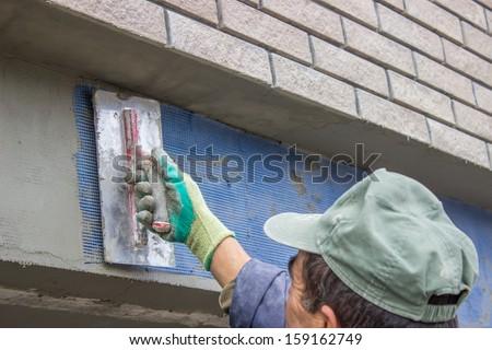 building worker sets plastic grid for plaster worker  - stock photo