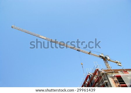 Building yellow tower crane in action against a blue sky
