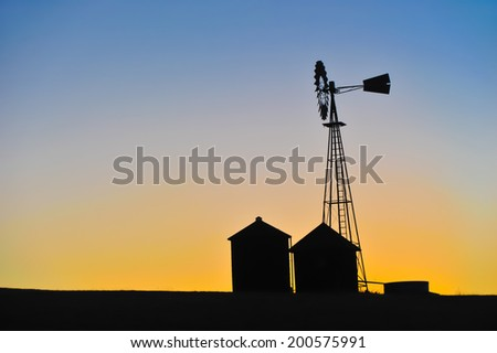 Buildings and a old fashioned windmill are silhouetted during sunset - stock photo