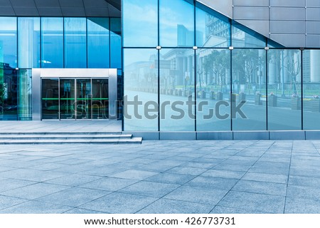 buildings and clean road reflected on the glass wall - stock photo