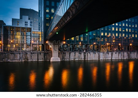 Buildings and pedestrian bridge over the Milwaukee River at night, in Milwaukee, Wisconsin. - stock photo