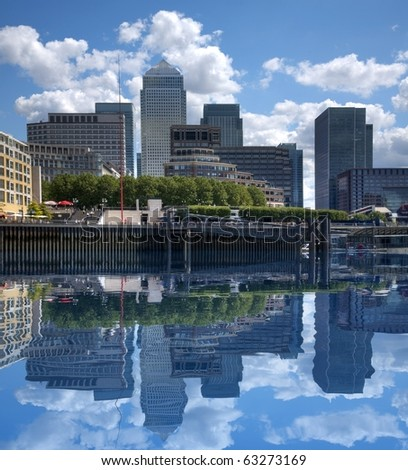 Buildings at Canary Wharf London reflected in the river Thames - stock photo
