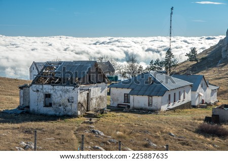 Buildings of abandoned military base in among steppe landscape Ai-Petri mountains with sea of clouds as background in evening lightning; south coast of Crimea peninsula, Russia,  - stock photo