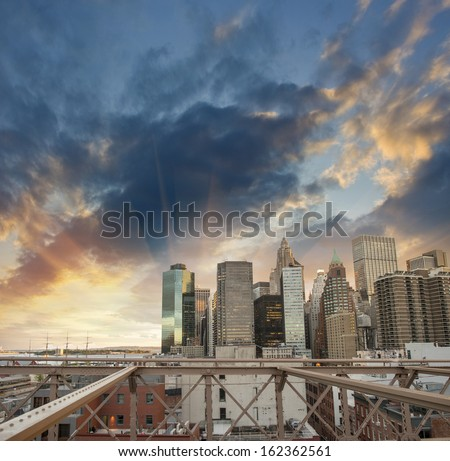 Buildings of lower Manhattan as seen from Brooklyn Bridge at sunset.