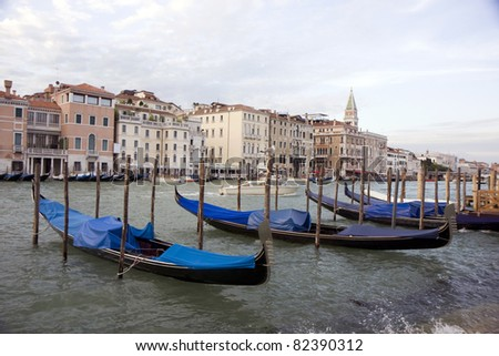 Buildings on the big canal of Venice, and parked gondola boats in Italy