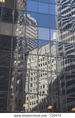 Buildings reflected in the glass face of a building.