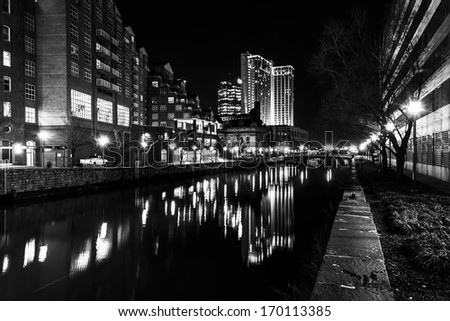 Buildings reflecting in the water at night in the Inner Harbor of Baltimore, Maryland. - stock photo
