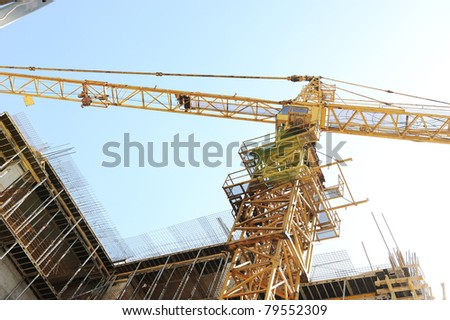 Buildings under construction and cranes under a blue sky - stock photo
