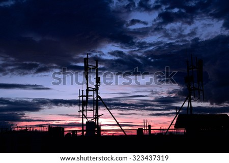 buildings with many antennas in a big city at sunset make silhouettes