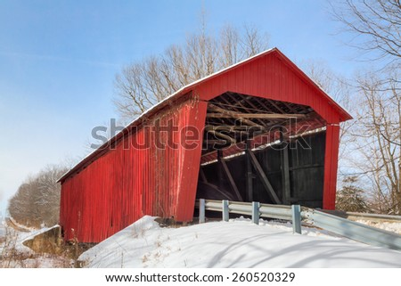 Built in 1922 in rural Putnam County Indiana, the Edna Collings Covered Bridge spans Little Walnut Creek surrounded by winter snow. This bridge is said by some to be haunted. - stock photo