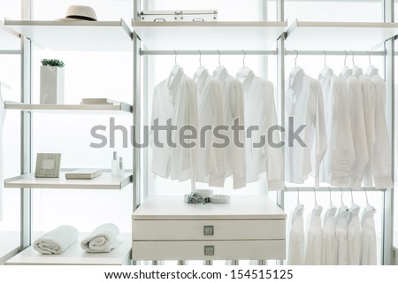 Built-in wardrobe Interior, with shirts, drawers, racks, frame, towel, hat, and book - stock photo