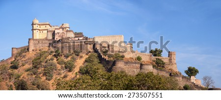 Built upon a hill, Kumbhalgarh Fortress, an old, 15th century Mewar redout with its crenelated battlements, stands watch over a valley in Western India. - stock photo