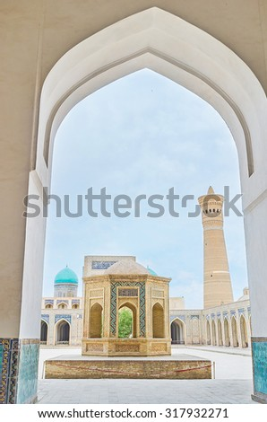 BUKHARA, UZBEKISTAN - APRIL 29, 2015: The view on the sheikh tomb and the cortyard of Kalyan Mosque from the arch, on April 29 in Bukhara, Uzbekistan.
