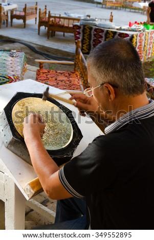 BUKHARA, UZBEKISTAN - AUGUST 17, 2015: Craftsman carving patterns on the metal plate, Bukhara, Uzbekistan, Central Asia - stock photo
