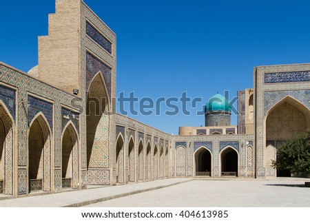 BUKHARA, UZBEKISTAN - AUGUST 10, 2015 - The courtyard of Kalyan Mosque decorated with glazed blue tiles and the sheikh tomb in front of the main portal, Bukhara, Uzbekistan, Central Asia