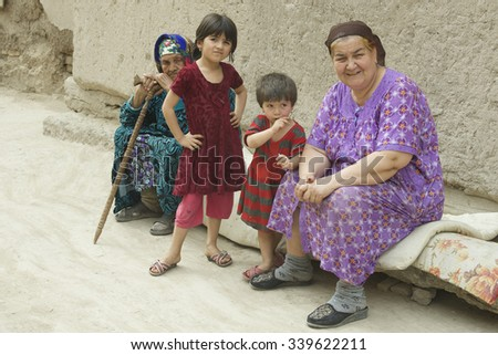 BUKHARA, UZBEKISTAN - May 16, 2015: Unidentified Uzbek family seats on a street in Uzbekistan, May 16, 2015. Family is the center of society in Uzbekistan