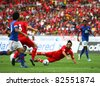 BUKIT JALIL - JULY 16 : Liverpool's Alberto Aquilani (red) falls after a tackle by a Malaysian defender in the game at the National Stadium on July 16, 2011, Bukit Jalil, Malaysia. Liverpool won 6-3. - stock photo