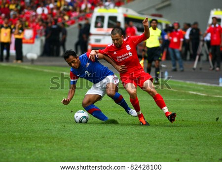 BUKIT JALIL - JULY 16: Mahalli Jasuli shields the ball from Liverpool's Joe Cole (red) in the game between Liverpool and Malaysia at the National Stadium on July 16, 2011, Bukit Jalil, Malaysia.