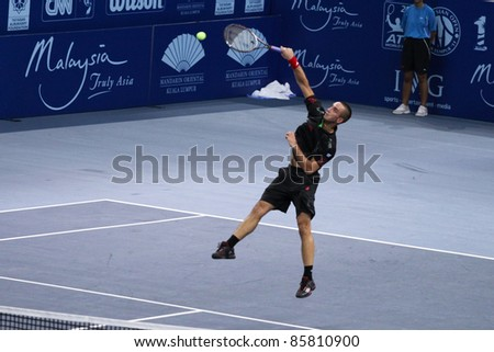 BUKIT JALIL, MALAYSIA- OCT 01: Serbia's Viktor Troicki smashes in this Malaysian Open semi-final match with Cyprus' Marco Baghdatis on October 01, 2011 in Putra Stadium, Bukit Jalil, Malaysia.