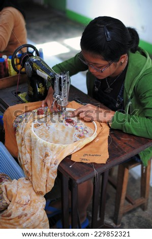 Bukit Tinggi, Indonesia - July 27 2009: Close up of woman sewing a flora pattern on the fabric. Kain Sulam is local traditional cloth and Bukit Tinggi is one of the best \\\\ - stock photo