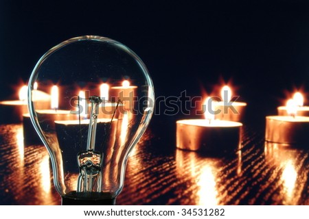 bulb and candle showing concept of saveing anergy