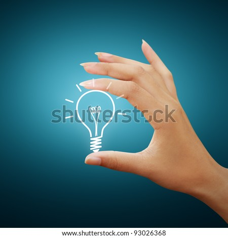 Bulb light drawing idea in woman hand - stock photo