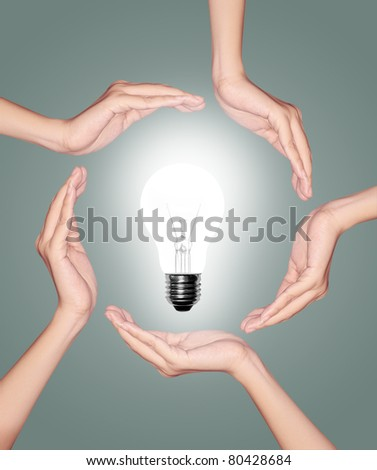 Bulb light in woman hand on green background - stock photo