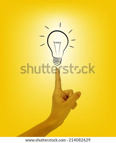 Bulb light on women Fingertip on yellow background  - stock photo