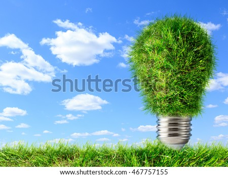 Bulb made of green grass on blue sky background