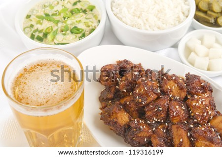 Buldak / Fire Chicken - Korean extremely hot fried chicken served with beer, rice, pickled radish, pickled gherkins and steamed eggs. - stock photo