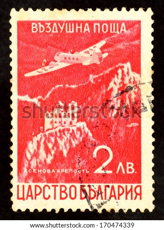 BULGARIA - CIRCA 1952: Red color stamp printed in Bulgaria with image of an airplane flying over the ancient Aspen's Fortress on the Rhodope Mountains. - stock photo