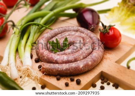 Bulgarian raw sausage with vegetables on wooden board, selective focus - stock photo