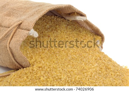 Bulgur wheat spilling out from a hessian sack, over white background.