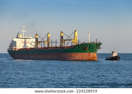 Bulk carrier and small tug boat in the Black Sea - stock photo