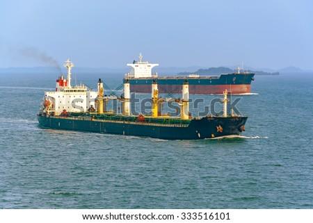 Bulk carrier cargo ship and oil tanker passes Strait of Singapore - stock photo